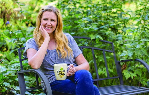Erika Bragdon sitting on a bench drinking a drink out of her mug