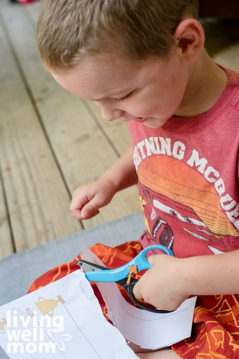 A 4 year old boy holding a pair of blue safety scissors, cutting along a straight line on paper.
