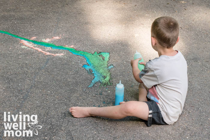 Young boy mixing blue and green sidewalk paint together