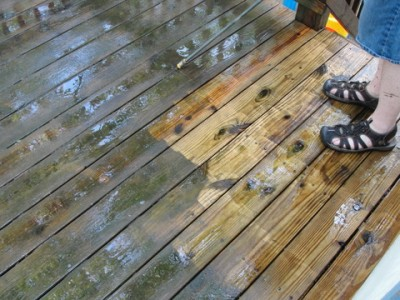 wooden deck boards partly clean partly dirty with man's feet