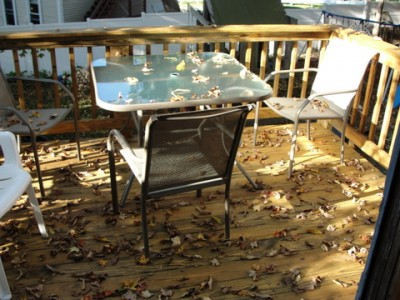 leaves falling on patio furniture and wood deck