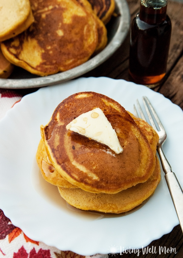 pumpkin spice pancakes with butter and maple syrup on a white plate