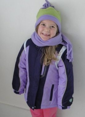 A little girl posing for a picture in snow gear