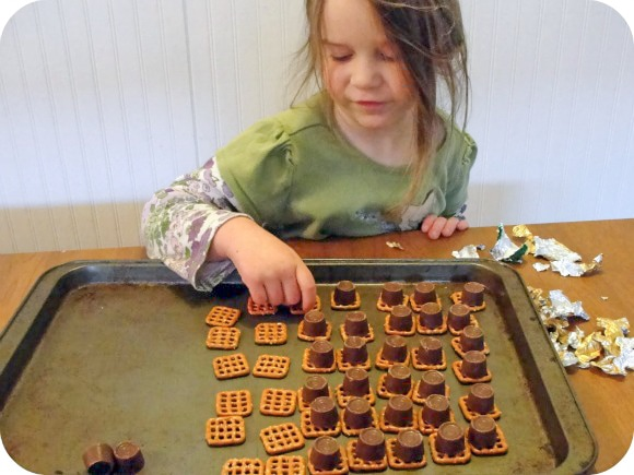 little girl putting chocolate onto pretzel squares