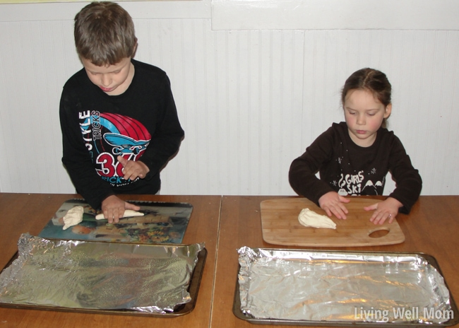 a little boy and girl forming shapes and letters with dough