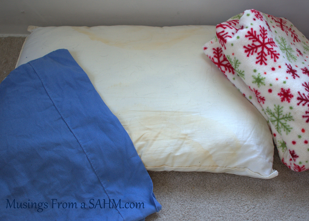 pillow with blanket and pillowcase on floor