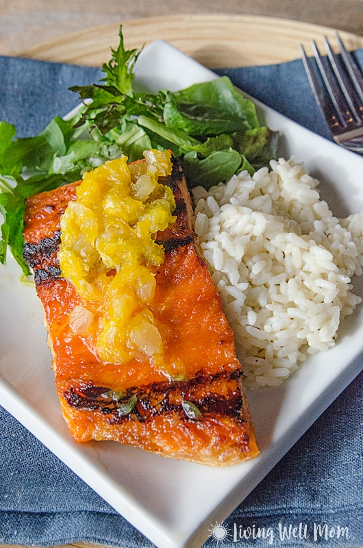baked salmon with orange glaze on a white plate with greens and rice
