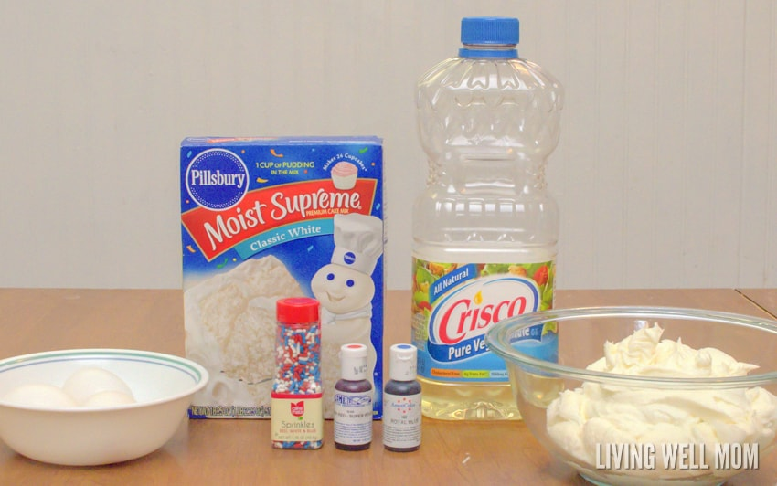 ingredients for cupcakes recipe - eggs in a bowl, cake mix, oil, sprinkles, frosting