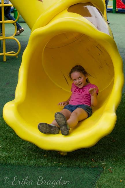 a little girl going down a slide
