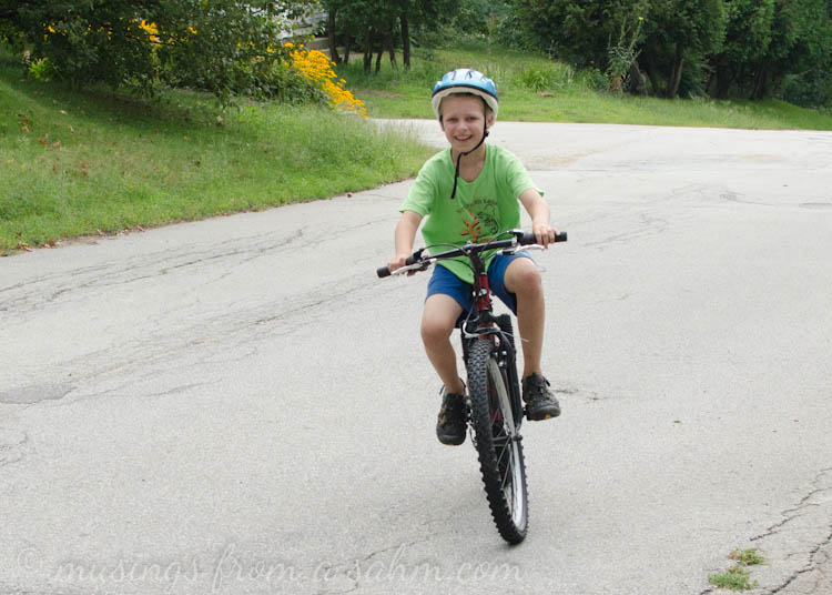 A young boy wearing a helmet and riding a bicycle