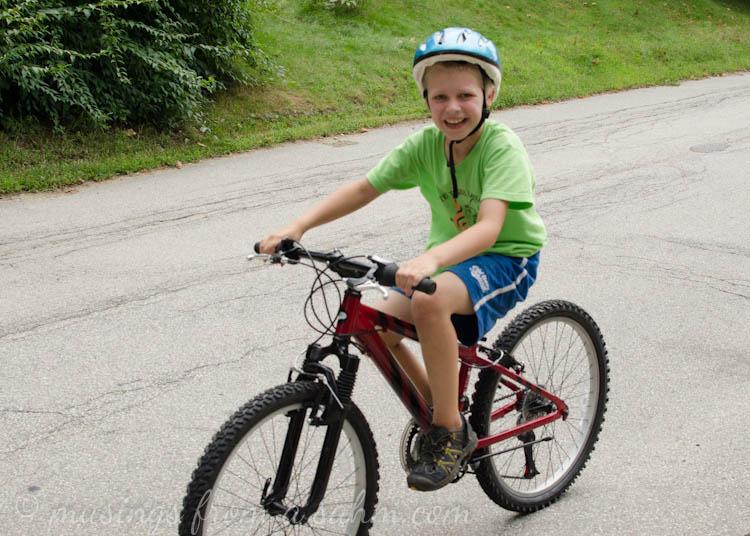 A young boy wearing a helmet riding a bike
