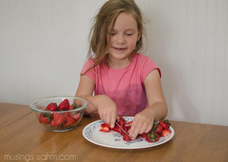 Emily cutting strawberries