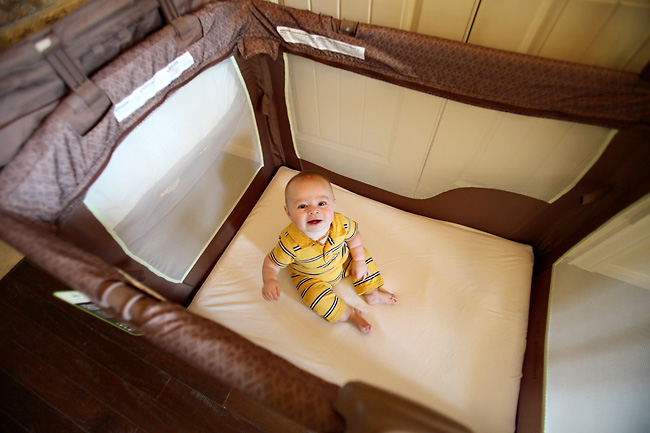 a baby sitting in a washable Playard