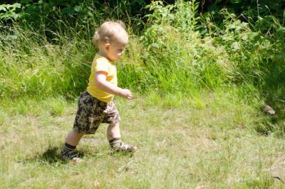 a little girl walking on grass