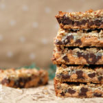 stack of magic cookie bars with beige spotted background and coconut flakes