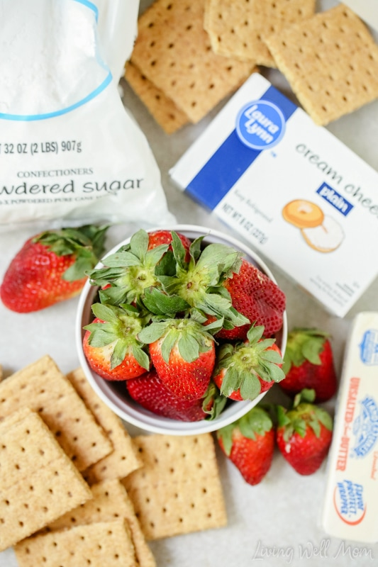 Ingredients for Strawberry Cheesecake cupcakes on a counter, including fresh berries.