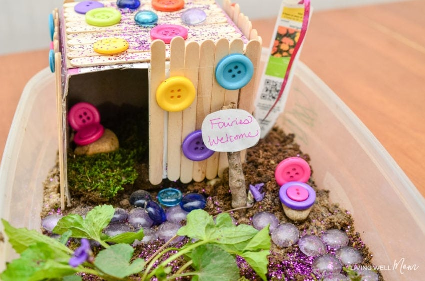 popsicle stick fairy house with dirt plants buttons and fairies welcome sign