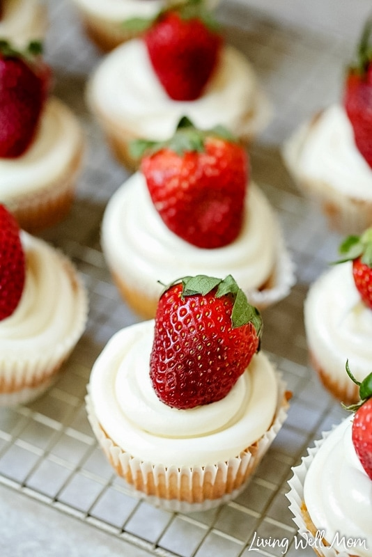 Whole strawberries atop a strawberry cheesecake cupcake.