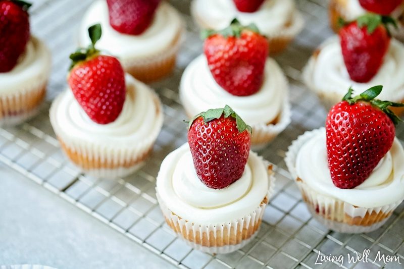 cupcakes topped with cheesecake frosting and whole strawberries