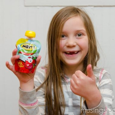 A little girl posing for a picture while holding a Motts snack & go applesauce