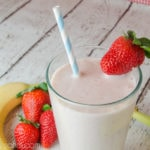 strawberry smoothie with straw and banana in a glass on white wood background