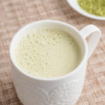 white mug with beige background matcha green tea latte