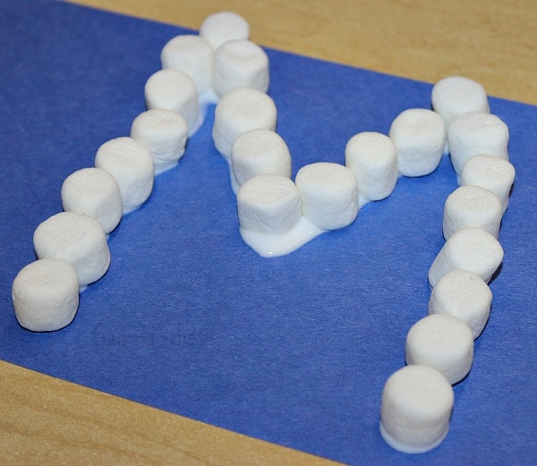 marshmallows glued to a blue construction paper In the shape of an M