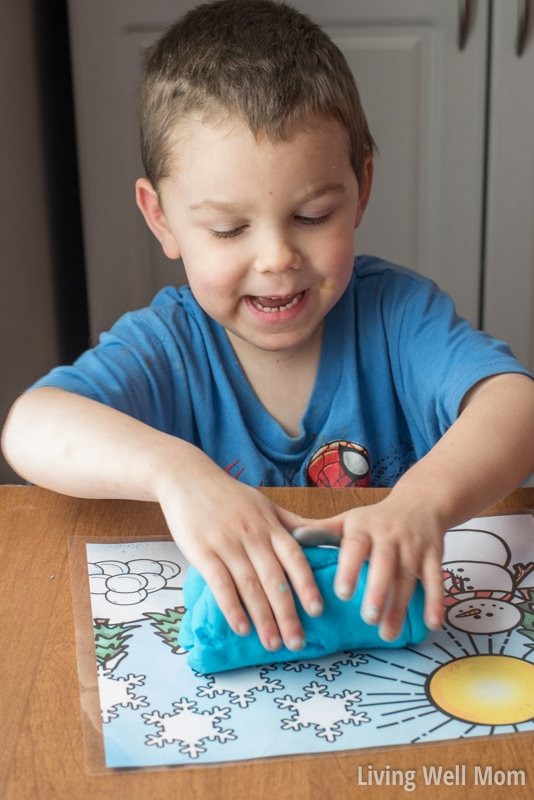 A young boy pressing playdough on top of a printable activity mat