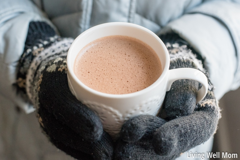 child holding cup of hot cocoa