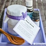 homemade lavender foot soak with label in purple tray with essential oils