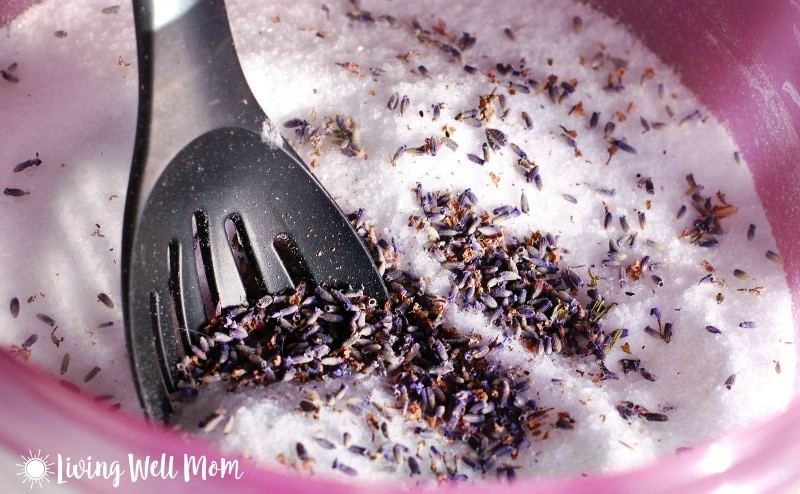 homemade Epsom salt foot scrub mixture with dried lavender and black spoon