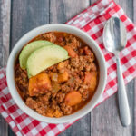 Beanless Turkey & Sweet Potato Chili in a bowl on checkered napkins with a spoon
