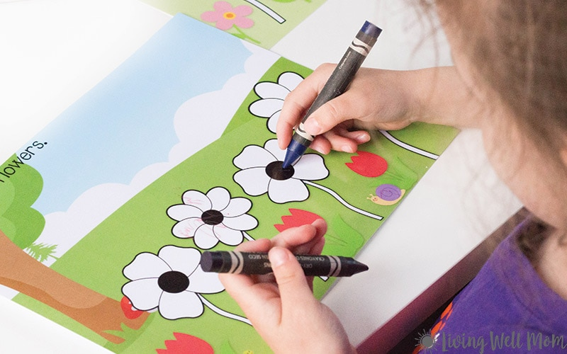child coloring flowers with crayons