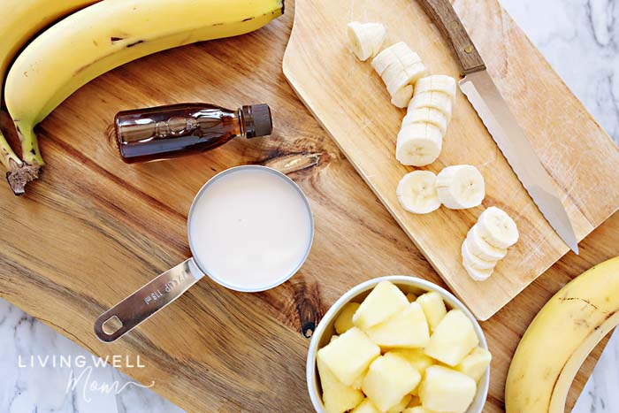 Dole whip ingredients including chunks of pineapple, slices of banana and a cup of coconut milk on a cutting board.