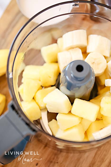 Fruit mixture of bananas and pineapple in a food processor.