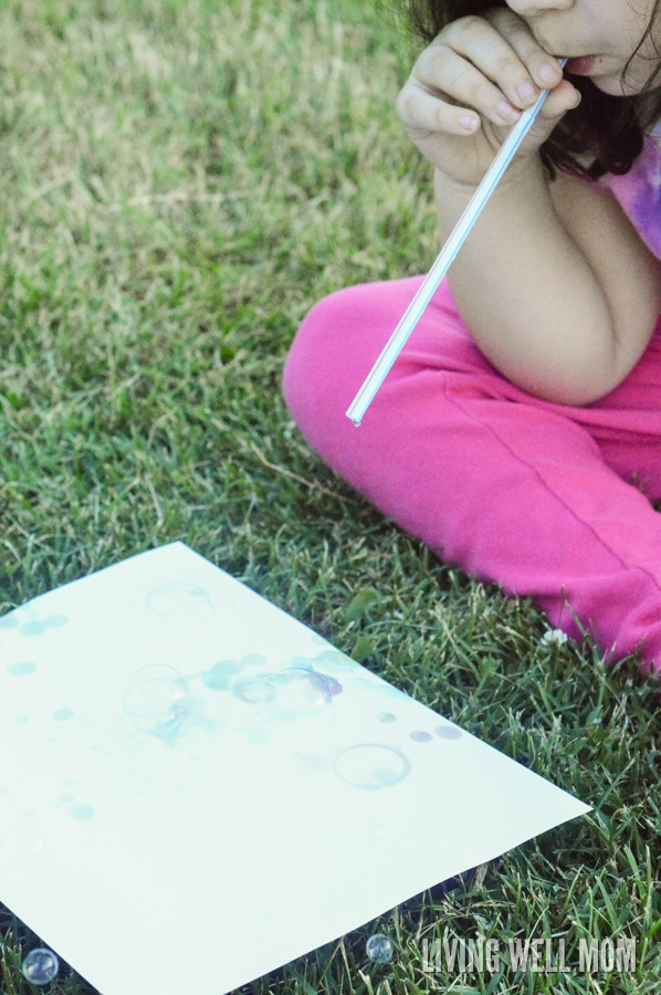 child blowing bubbles with straw onto paper for bubble activity