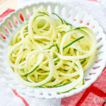 A close up of zucchini noodles on white plate