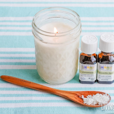 white citronella candle in mason jar with brown wood spoon and essential oil bottles