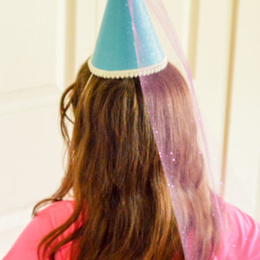 a girl with long brown hair and blue princess hat