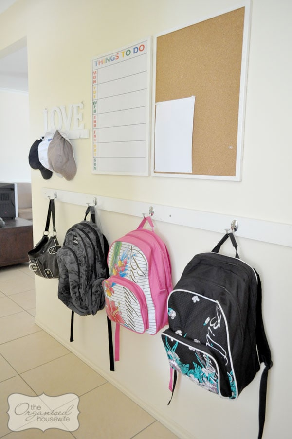 backpack storage command center with bulletin board and calendar on the wall