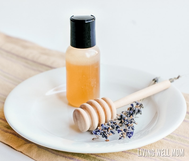 homemade honey face wash in a small bottle on a white plate with lavender flowers and honey scoop