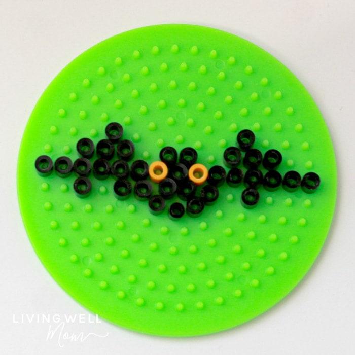 bat perler bead pattern on green board