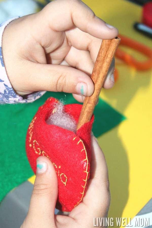 These Felt Apple Ornaments are easy for kids to put together and they have a secret - they're cinnamon-scented! Perfect for a homemade teacher gift, these DIY ornaments are a great craft activity for kids or a first sewing project.