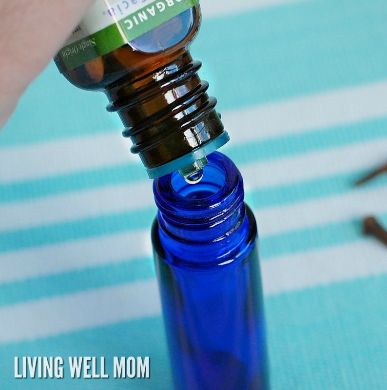 adding drop of essential oil to a blue glass bottle