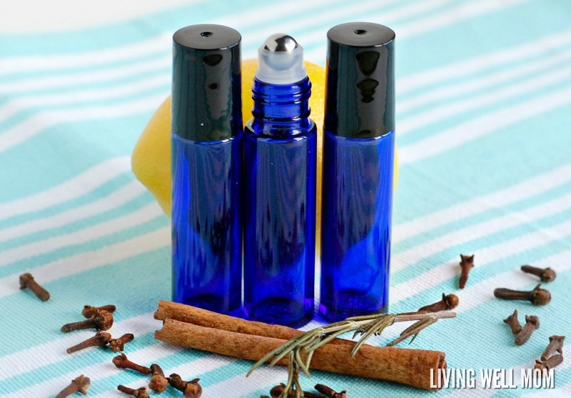 3 essential oil roller bottles with lemon, dried cloves and cinnamon stick on blue tablecloth