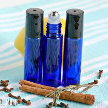 blue essential oil roller bottles with cinnamon stick and lemon on blue tablecloth