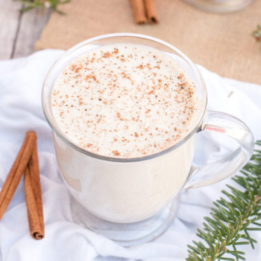 homemade vegan eggnog in a glass with cinnamon sticks and pine branches