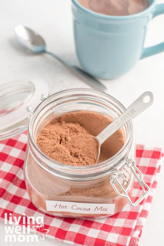 homemade cocoa mix in glass container with red checkered napkin and blue mug
