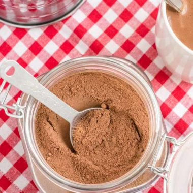 homemade cocoa mix in glass container on red checkered napkin with mug of cocoa