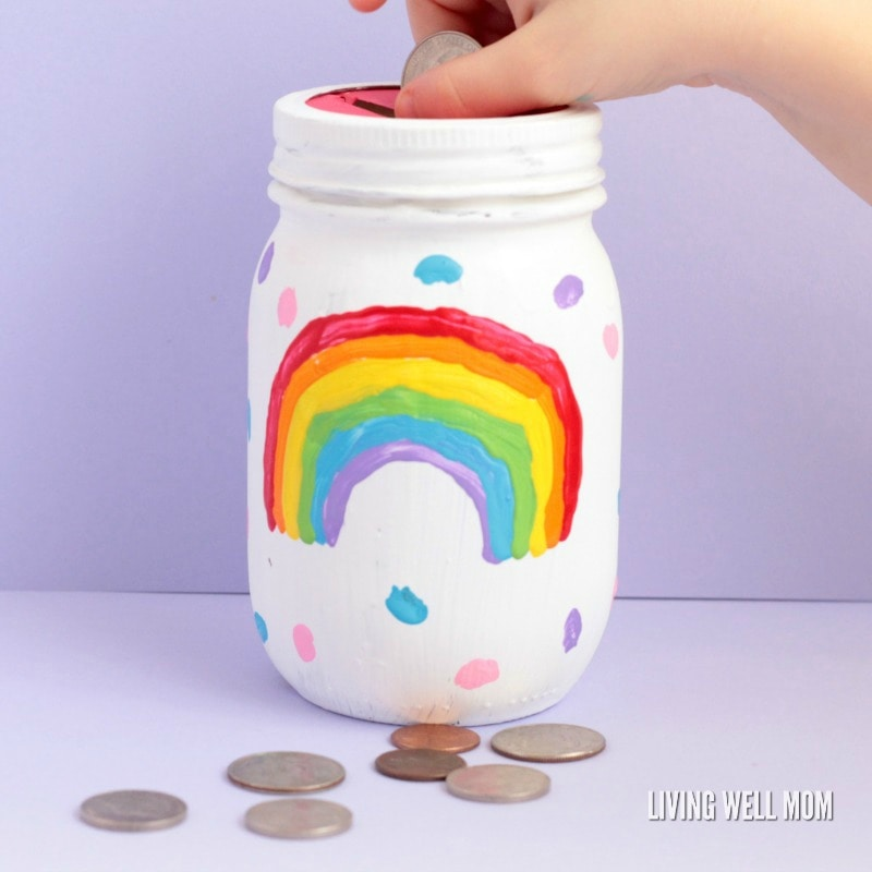 This DIY rainbow mason jar piggy bank is easy enough for kids to make themselves! It's a fun, colorful way to encourage kids to save money.